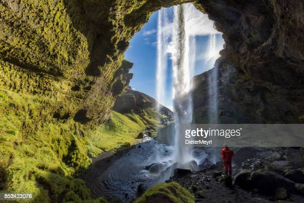 Hiker at Majestic Kvernufoss Waterfall in Iceland