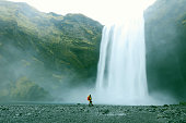 A female hiker is standing at a foot of a Skogafoss waterfall in Southern Iceland. Traveller looks very small in perspective with this majestic waterfall. Skogafoss is one of the best known and most p