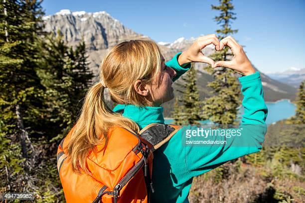 Hiker at mountain top making heart shape