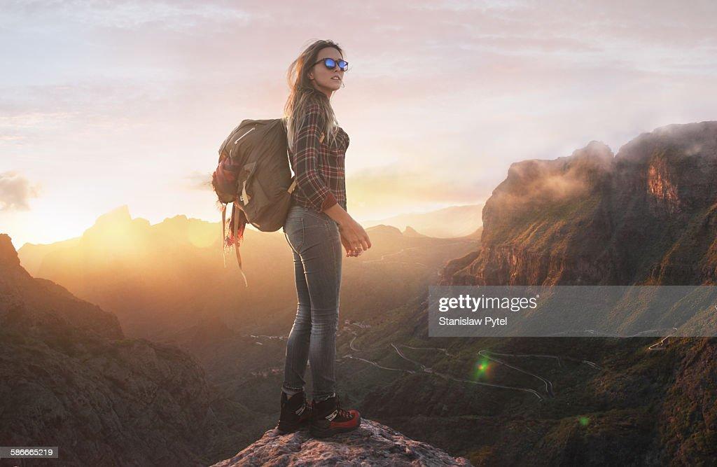 Hiker at summit peak, looking at sunset : Stock Photo
