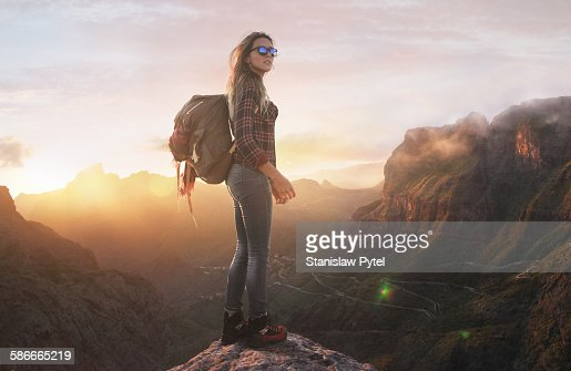 Hiker at summit peak, looking at sunset