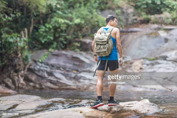 Hiker backpack adventure at  waterfall  the forest.
