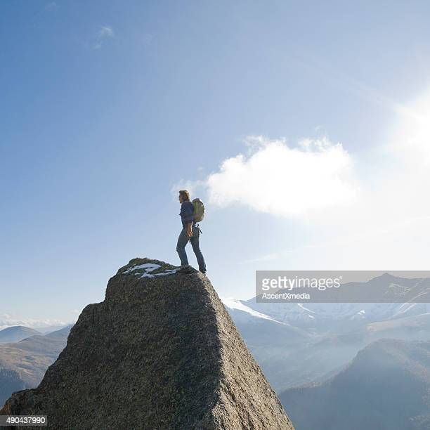 Hiker balances on rock summit above mountains