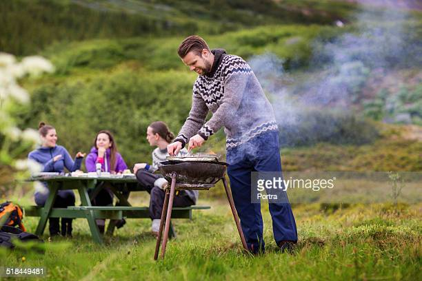 Hiker barbecuing for friends on grassy landscape
