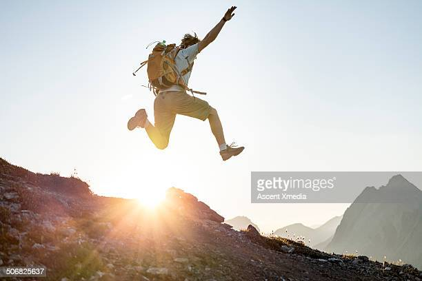 Hiker bounds along ridge crest, at sunrise