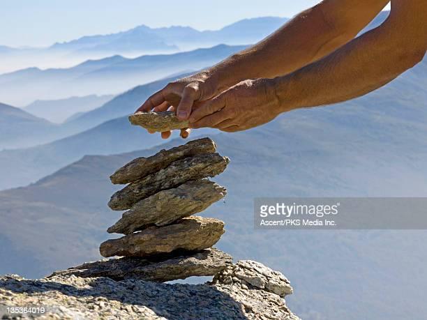 Hiker builds rock cairn high above distant mtns