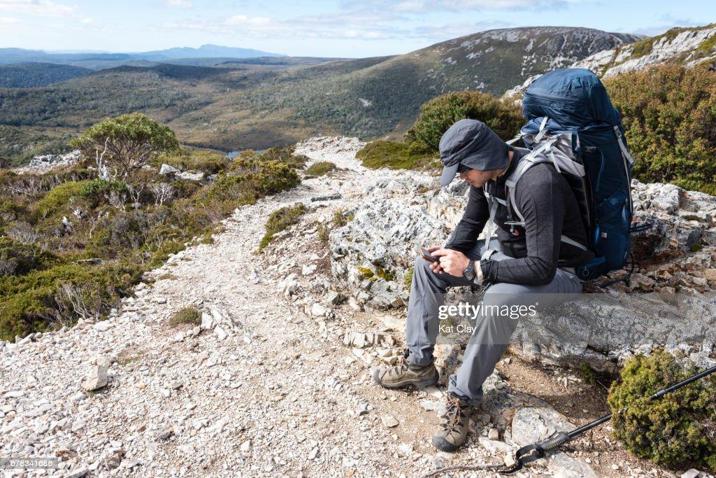 Hiker checking smart phone : Stock Photo