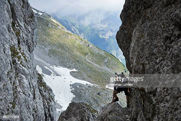 A hiker climbs a via ferrata on his way to the 'Lampsenspitze' at the Karwendel region on June 13 2014 near Vomp Austria The Karwendel is the largest...