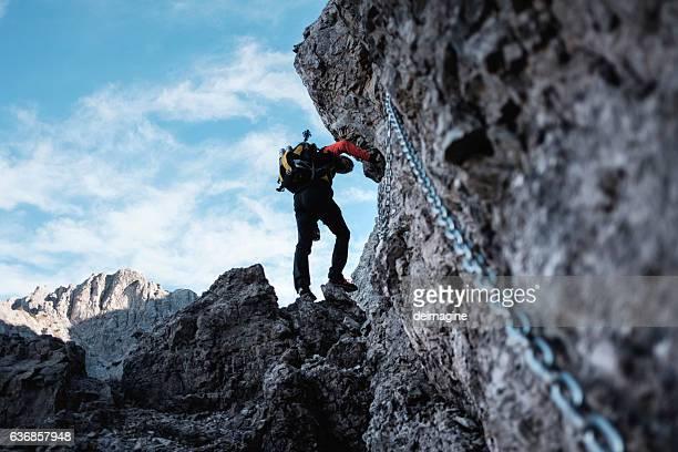 Hiker climbs through a path with chains