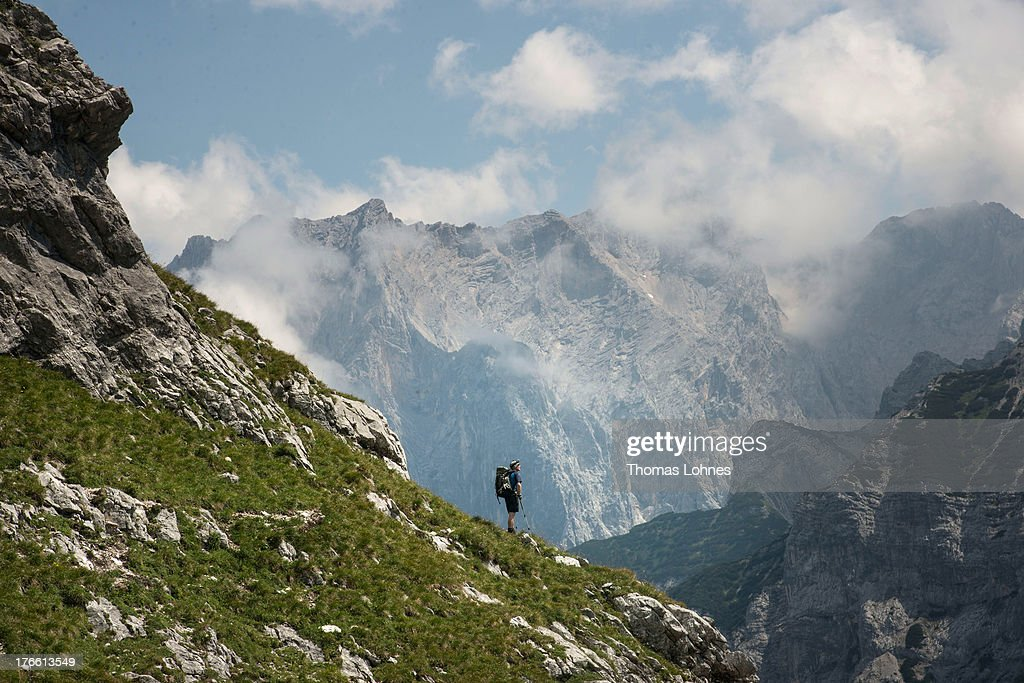 A hiker coming from Germany's highest mountain Zugspitze, takes a break and looks to the mountains of the Reintal in the Alps near the village of Garmisch-Partenkirchen during nice weather on August 15, 2013 in Garmisch-Partenkirchen, Germany.