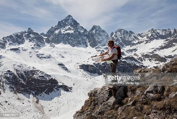 A hiker consults a map, standing on mountain ridge