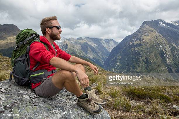 Hiker contemplating nature from mountain top