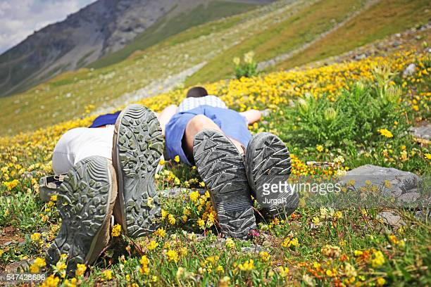 Hiker Couple Lying on Alpine Wildflower Meadow in Swiss Mountains