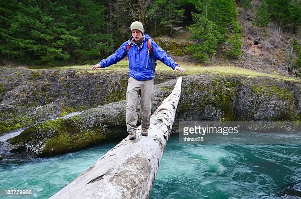 Hiker crossing log
