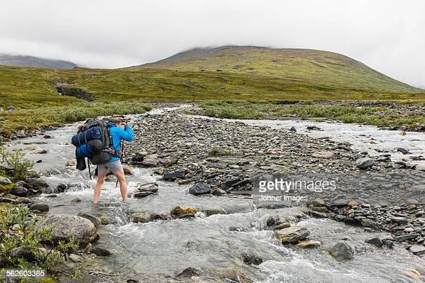 Hiker crossing river