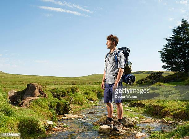 Hiker crossing rocky stream in countryside.