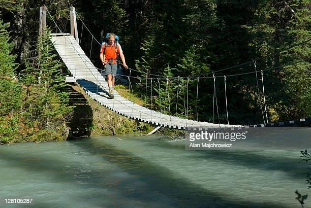 Hiker crossing suspension bridge over Helmet Creek, Kootenay National Park, British Columbia, Canada