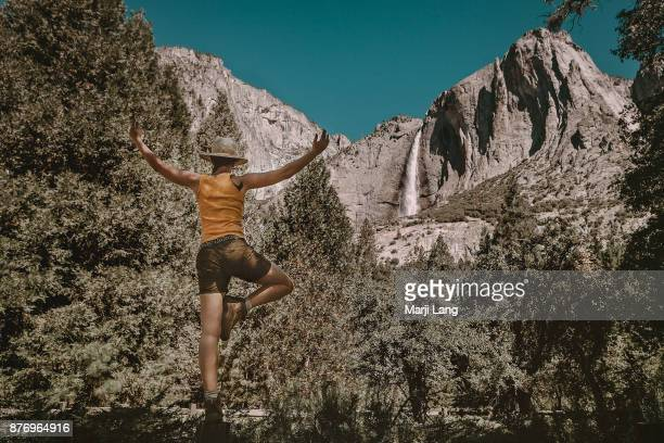 Hiker doing a balancing exercise by the Bridalveil waterfalls in Yosemite National Park California USA