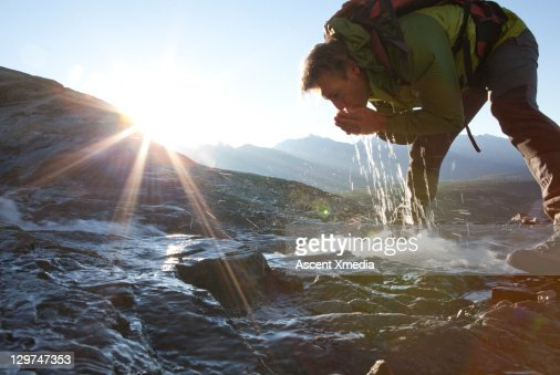 Hiker drinks from mountain stream at sunrise.