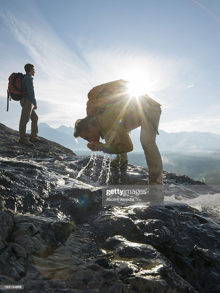 Hiker drinks from steam while companion looks out