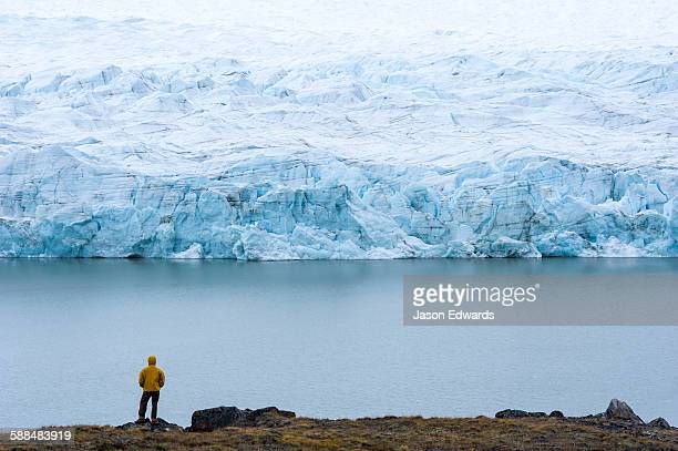 A hiker dwarfed by the fracture zone of a glacier on the Greenland Ice Sheet.