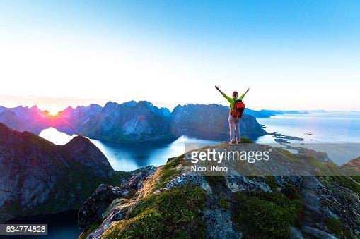 北極夏、レーヌ、ノルウェーのロフォーテン諸島の間に真夜中の太陽を楽しむハイカー : ストックフォト