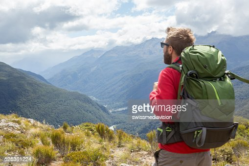 Hiker enjoying view from mountain top, Milford sound, New Zealand