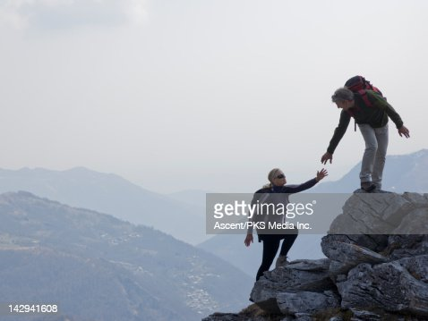 Hiker extends helping hand to partner, rock ridge : Stock Photo