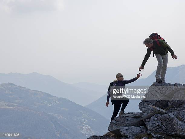 Hiker extends helping hand to partner, rock ridge