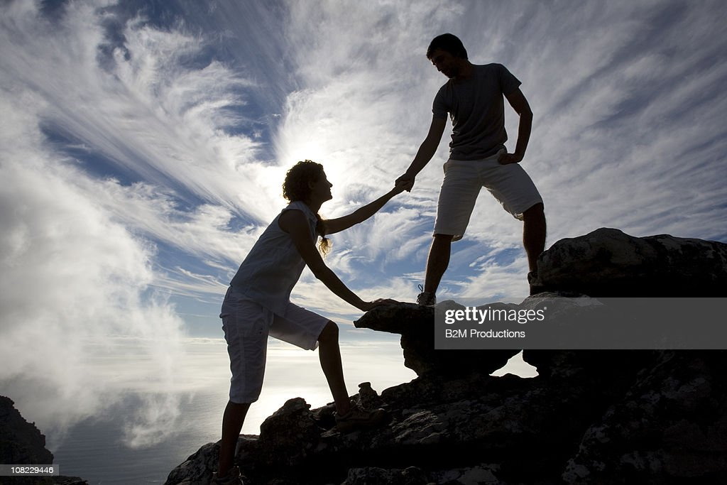 Hiker extends helping hand to teammate : Stock Photo