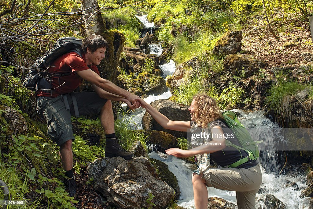 hiker extends helping hand to woman : Stock Photo