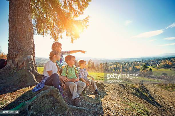 Hiker family resting under tree