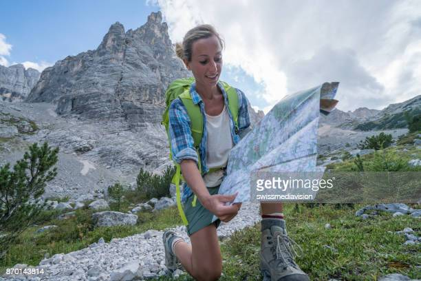Hiker female consulting trail map, Dolomites, Italy