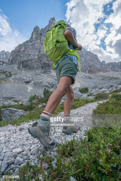 Hiker female on mountain trail moving up, mountain peak