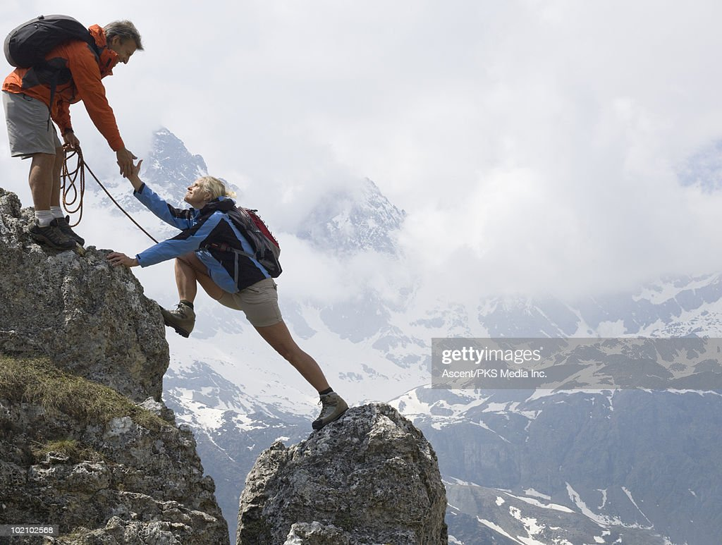Hiker gives assistance to teammate on rock ridge : Stock Photo