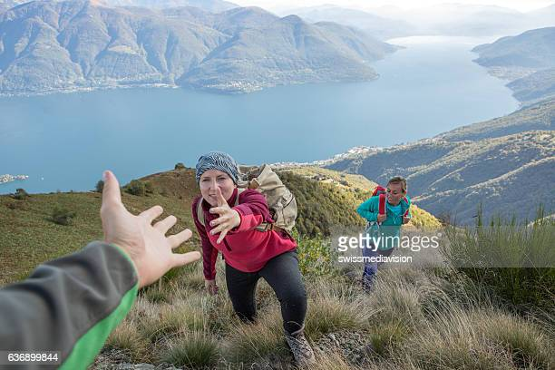 Hiker giving helping hand to teammate