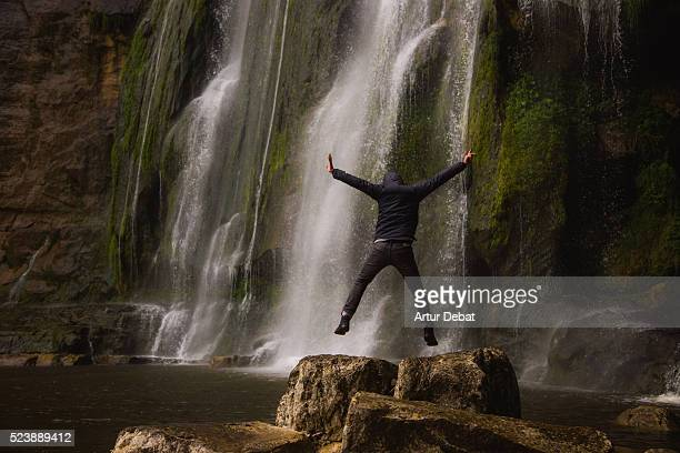 Hiker guy jumping under a beautiful 100 meters tall waterfall with curtain of water over the crag during the rainy season in the Catalan mountains during a outdoor adventure.