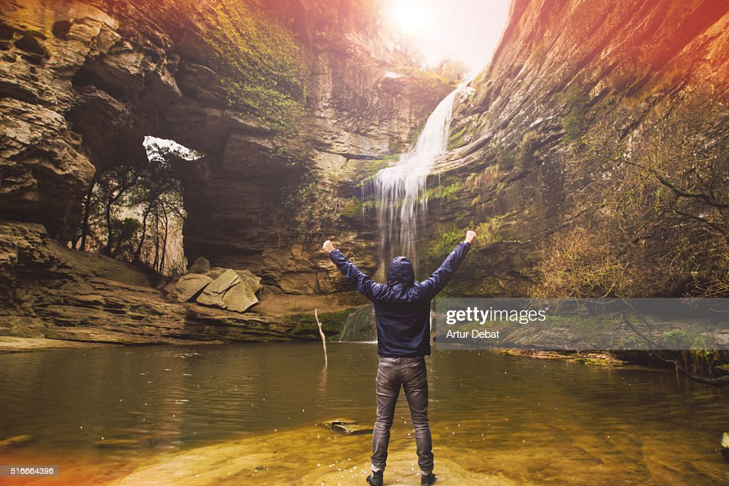 Hiker guy raising arms excited in front of a stunning horsetail waterfall during a alone nature journey adventure.