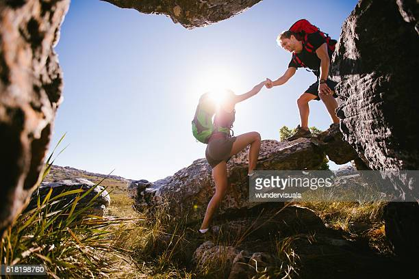 Hiker helping woman climbing rock while hiking in nature