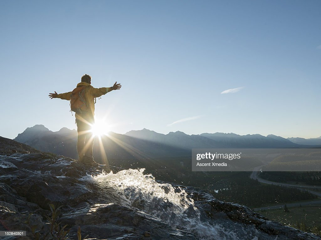 Hiker holds arms outstretched above mtns, sunrise : Stock Photo