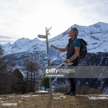 Hiker holds map, looks at directional sign : Stock Photo