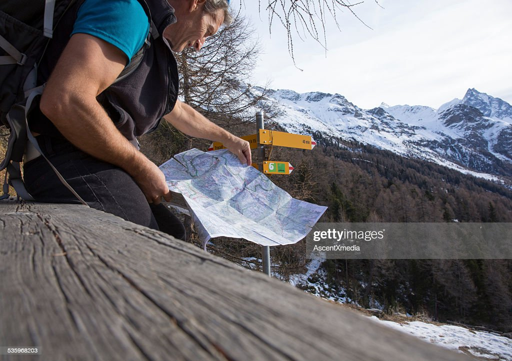 Hiker holds map on bench, below directional sign : Stock Photo