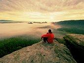 Hiker in black on the rocky peak. Wonderful daybreak in mountains, heavy orange mist in deep valley. Man on the rock watch over the fog .