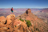 A young male hiker is standing on a rock enjoying the amazing view over famous Grand Canyon with the Colorado river flowing on a beautiful sunny day in summer, Arizona, USA