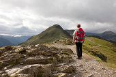 A male hiker admires the view from the top of Catbells in the Lake District National Park, Cumbria, England.