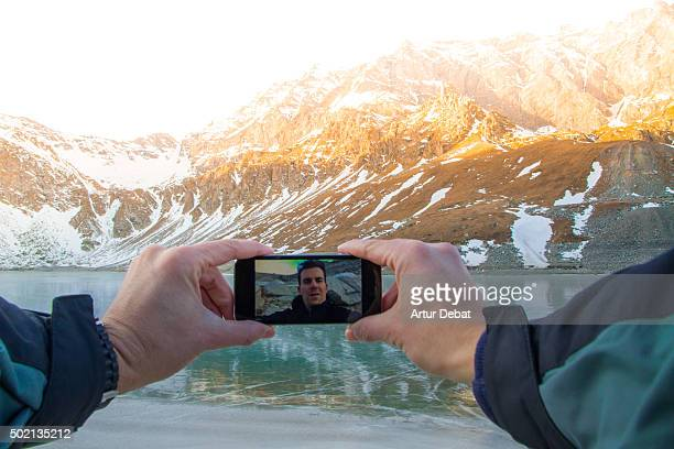 Hiker in the Gran Paradiso national park taking a selfie from point of view with the frozen lake with beautiful reflection on sunset .