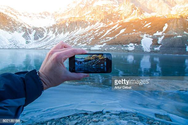 Hiker in the Gran Paradiso national park taking pictures of the frozen lake with beautiful reflection on sunset .