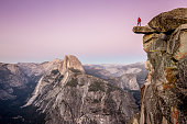 A fearless male hiker is standing on an overhanging rock at Glacier Point enjoying the breathtaking view towards famous Half Dome in beautiful post sunset twilight in summer, Yosemite National Park, C