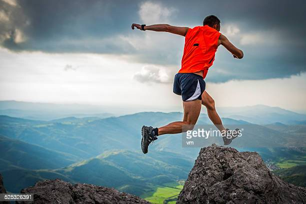 Hiker Jumping from One Rock to Another