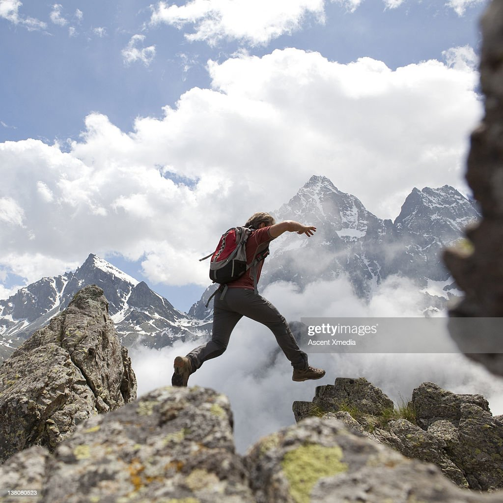 Hiker jumps across rock gap, mountains behind : Stock Photo